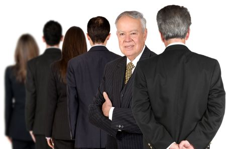 business male senior facing the camera with his team behind him