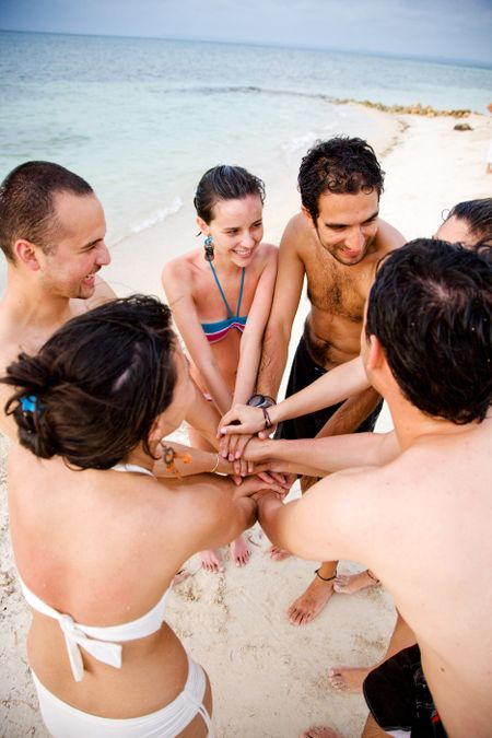 happy group of friends smiling outdoors at the beach with their hands together