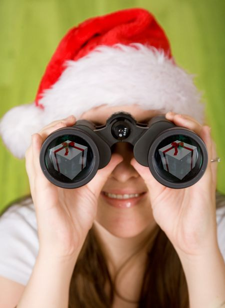 female santa searching for gifts - note the gifts on the binoculars lens reflection