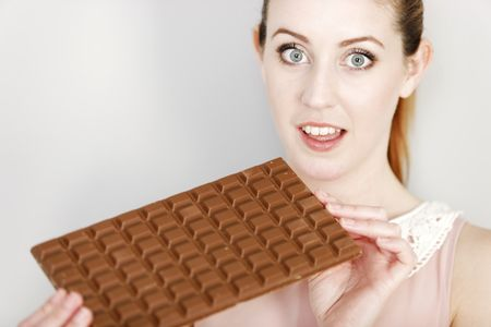 Attractive young woman enjoying a large chocolate bar.