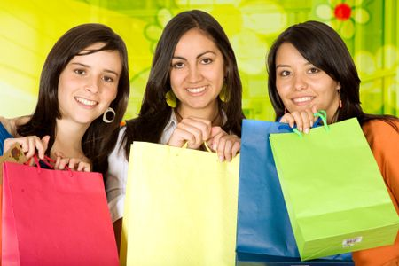 girls with shopping bags in front of a green glass background