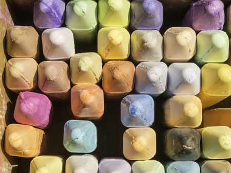 Overhead view of pastel-colored chalk sticks in open box used by sidewalk artist on a sunny afternoon