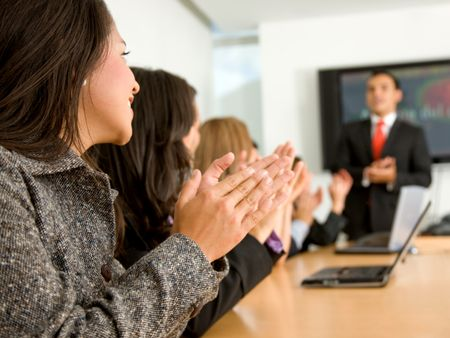 business people in an office clapping a presentation