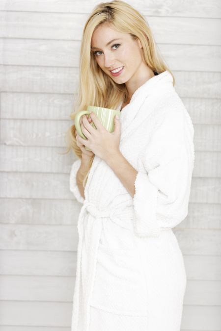 Beautiful young woman in a white robe enjoying a hot drink