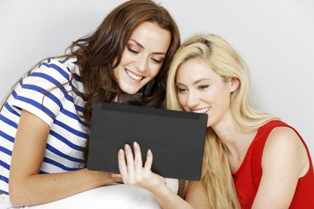 Two young friends using a computer tablet together