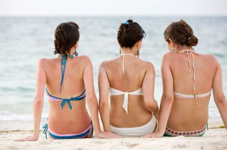 female friends at the beach relaxing and looking at the ocean