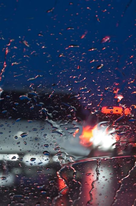 Rear of car seen through windshield in rain