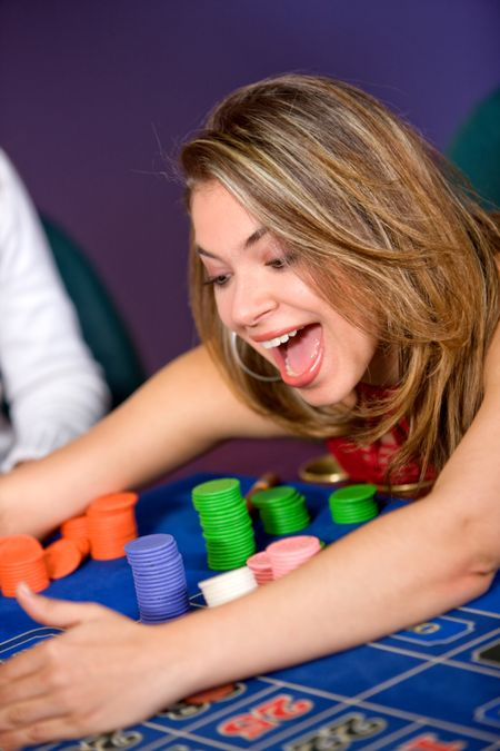 woman in a casino gambling and winning on the roulette