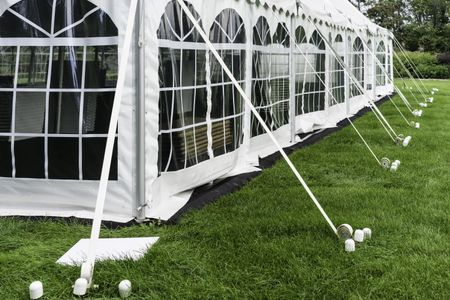 Corner and side of large white event tent with plastic windows, anchored on garden lawn in summer