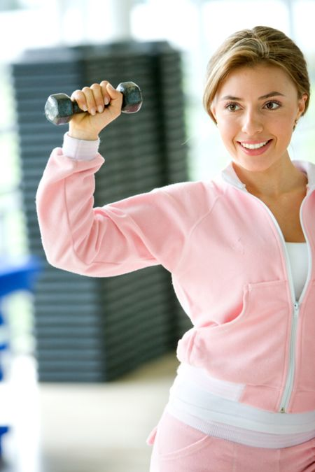 beautiful woman at the gym exercising with small free weights