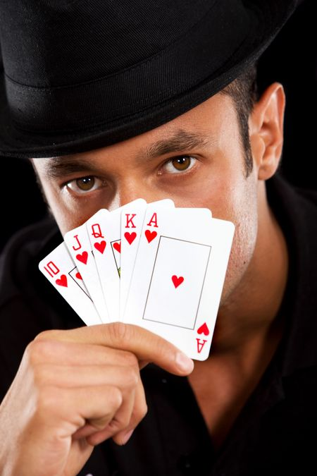 male magician covering his face with cards - isolated over black