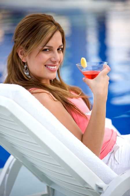 beautiful woman having a cocktail drink by the swimming pool