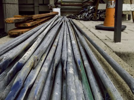 Abstract illustration of long steel bars and other equipment for assembly of scaffolding on a construction site