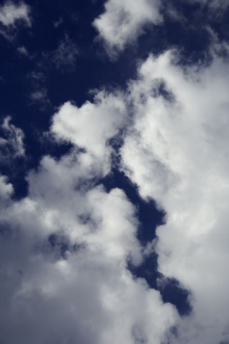 Rift in cumulus clouds in blue sky