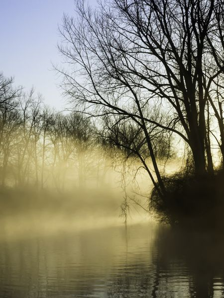 Promise of peaceful illumination: Rays from rising sun light up morning mist over a quiet river early in northern spring