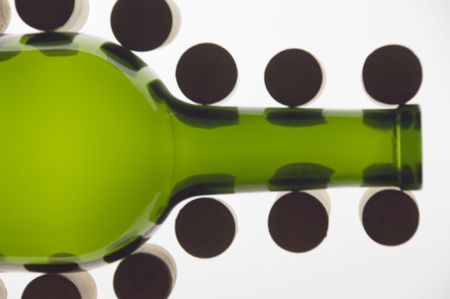Green wine bottle flanked by corks on end