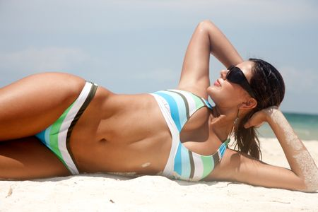 bikini girl lying on a sandy beach while on vacation