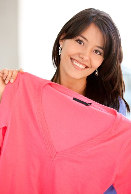 Casual woman smiling and shopping clothes in a store