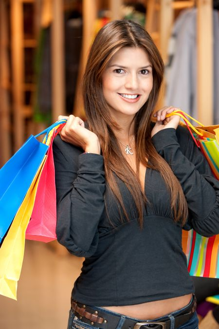 Beautiful woman with shopping bags in a mall smiling