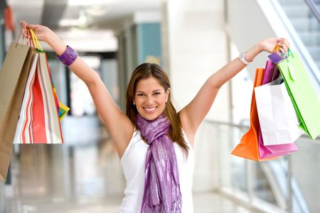 Girl holding shopping bags in a mall smiling