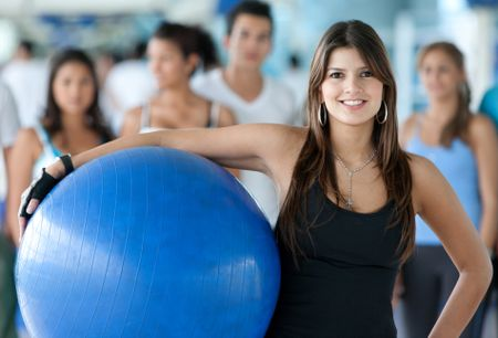 Gym woman with a pilates ball standing in front of a group