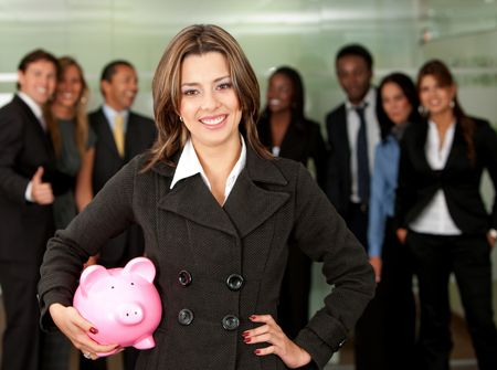 business woman holding a piggy bank at her office - business concepts