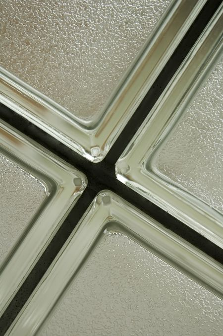 Corners of four opaque bathroom windows with silver frames