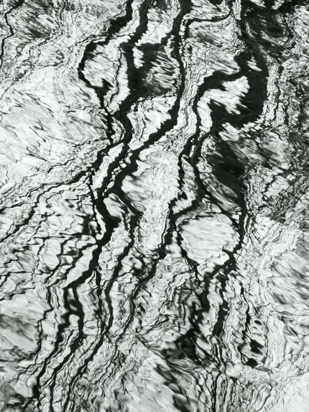 Aquatic abstract in autumn: Distorted reflection of bare trees on surface of stream, in black and white