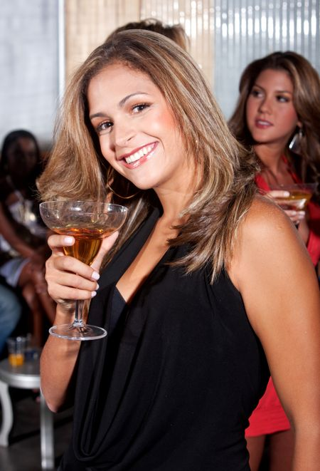 Happy woman at a party smiling and holding a cocktail drink