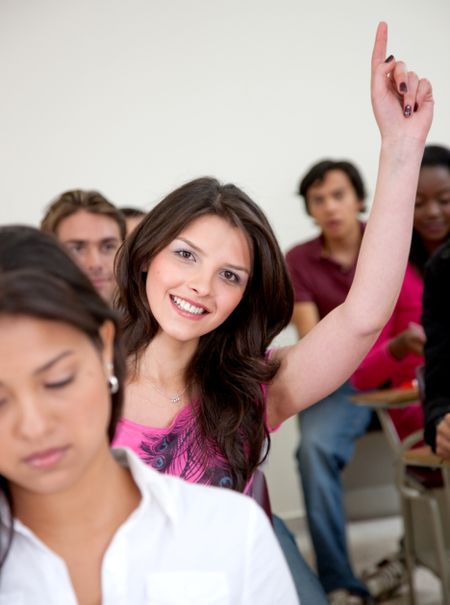 Female student in a classroom - participating and smiling