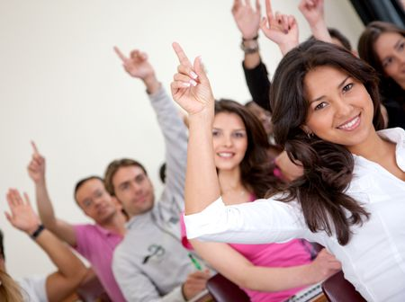 Group of university students in a classroom rising their hands