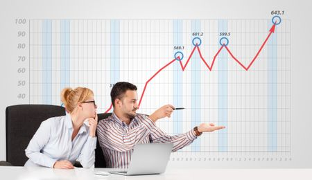 Young businessman and businesswoman calculating stock market with rising graph in the background