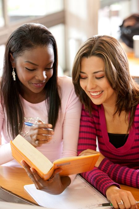 Couple of female students with a book in a classroom
