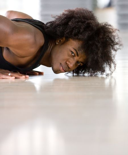 Attractive black man in a gym doing push ups - side view