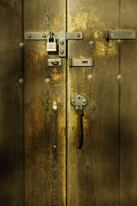 Detail of antique wooden door with padlock and hardware on restored Victorian house built in 1858 and now maintained as a public museum