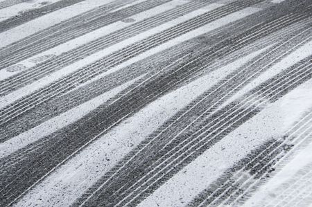Multiple tracks of car tires, with a few footprints, in snow on pavement