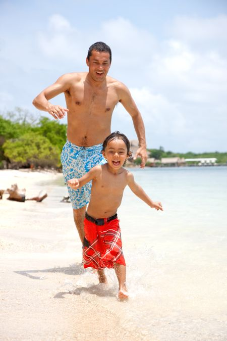 Man and son running on the beach