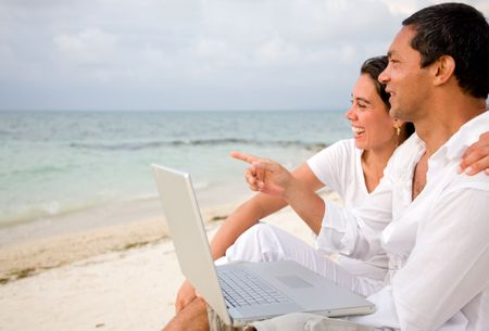 Beach couple on a laptop during vacations