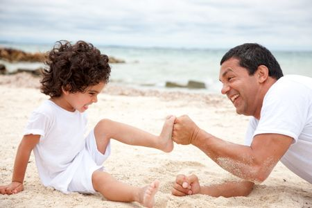 Man and son at the beach competing