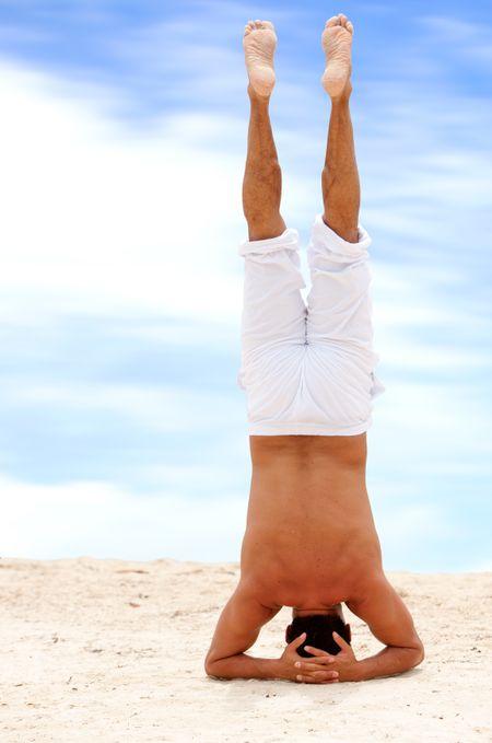 Fullbody man doing yoga on the beach