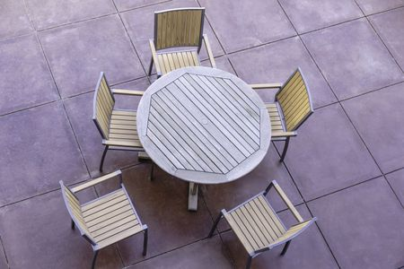 Geometric patterns for casual conversation outdoors: High angle view of wooden round table and five outdoor chairs on large flagstone patio in the American Southwest