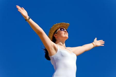 girl with open arms enjoying her freedom over a blue sky