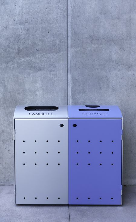 Landfill and recycle bins, one silver one blue, by exterior gray concrete wall on university campus