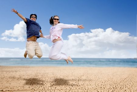 couple in love jumping of joy at the beach on a sunny day