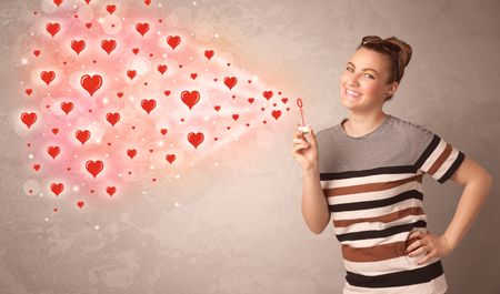 Pretty young girl blowing valentine red heart symbols