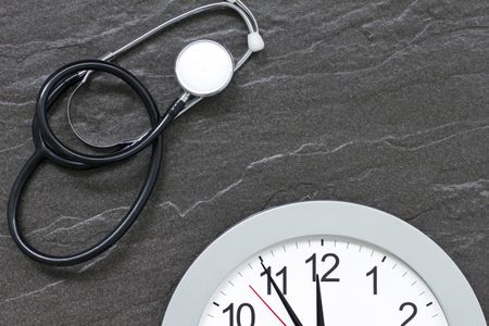Concept showing doctors stethoscope and a clock face simulating an appointment