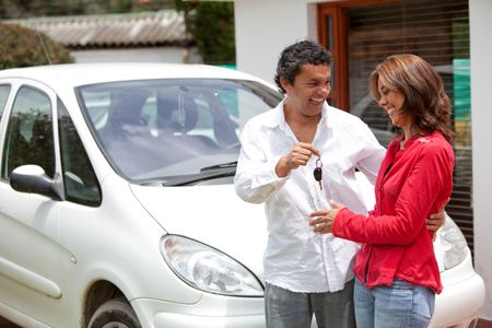 Man handing over the keys of their car to his wife