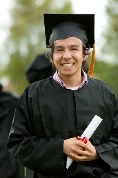 graduation man portrait smiling and looking happy outdoors