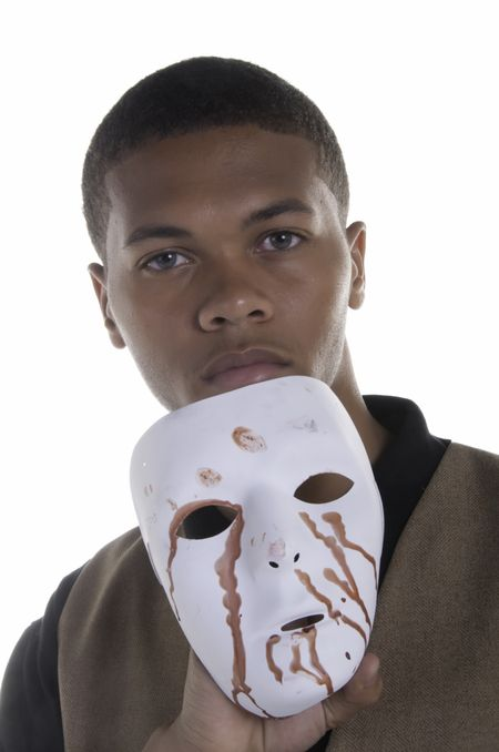 Handsome black man holding blood-stained white mask below his face