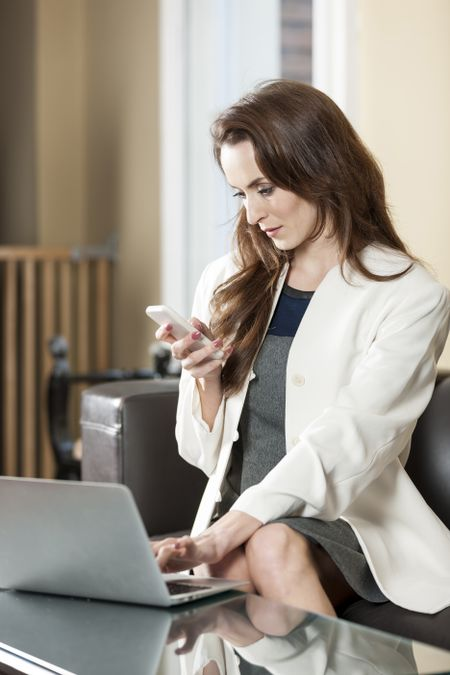 business woman using her laptop while using her mobile phone